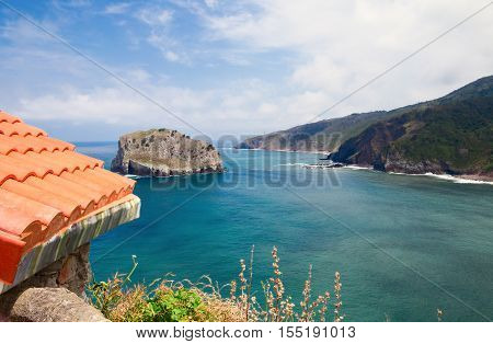 rocky ocean coast and part of a roof. A view of the ocean in summer sunny day at the left in the foreground a part of a tile roof