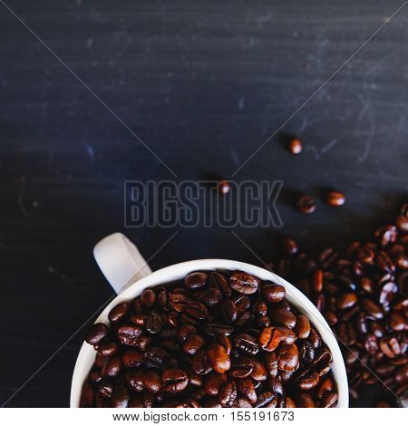 Roasted coffee bean in white cup with hot espresso drink on dark background. Low key, Vintage tone, From above