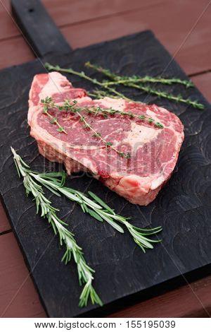 Raw rib-eye steak on black cutting board