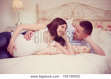 Happy Young Pregnant Couple In Bedroom
