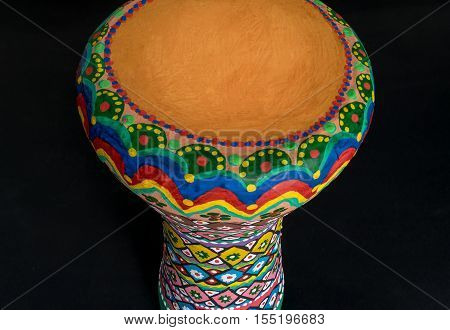 High angle of a colorful painted goblet drum (also chalice drum tarabuka darbuka debuka doumbek dumbec dumbeg dumbelek toumperleki or tablah) on black background a single head membranophone with a goblet shaped body used mostly in the Middle East North Af