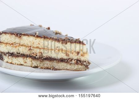 piece of delicious cake drizzled with chocolate on a white background