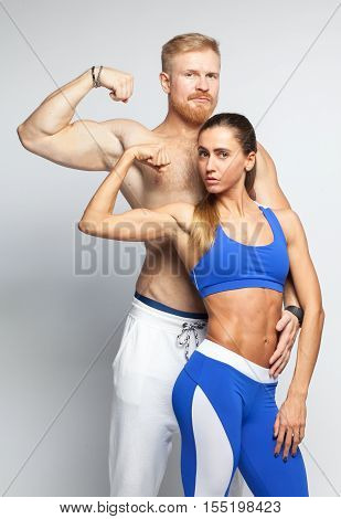 Sporty Couple Showing Their Muscles