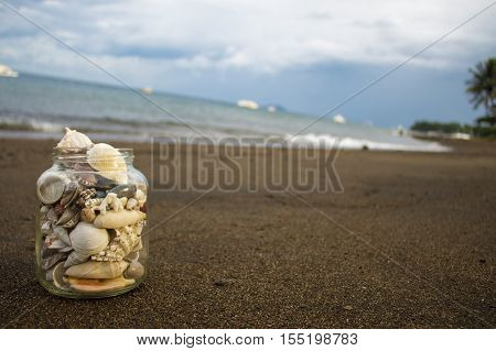 Seashells collection on the sand beach. Experimental composition with diagonal horizon. Tropical landscape with sea and white boats with place for text.
