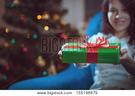 Beautiful girl with gifts on the background of Christmas trees