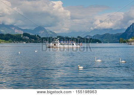 Lucerne Switzerland - May 24 2016: Excursion boat MS Triton and swans in front of hidden by clouds snow covered Alps mountains peaks on Lake Lucerne Switzerland.