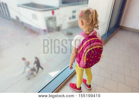 Little Girl Looking Through The Window