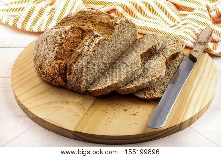 sliced irish soda bread on a wooden plate and bread knife