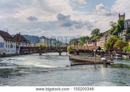 Lucerne Switzerland - May 24 2016: Architecture of Lucerne. River Reuss and wooden ancient Spreuer Bridge in the old town of Lucerne Switzerland.