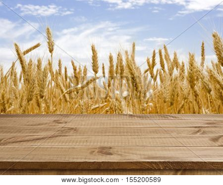 Wooden table surface over defocused golden wheat field landscape background
