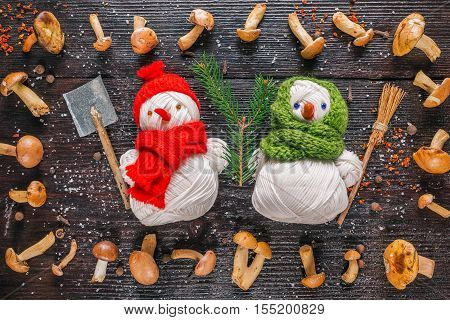Pair of handmade yarn snowmen in the frame of fresh bovines mushrooms and spices on the dark wood surface
