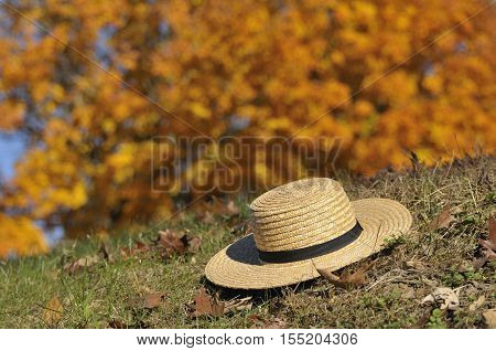Amish straw hat laying over fall leaves with colorful fall tree in the background