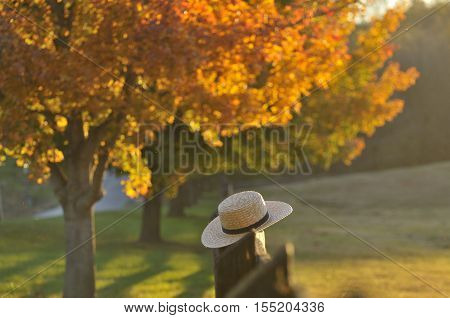 Amish straw hat laying over farm fence post on hazy fall evening in Pennsylvania