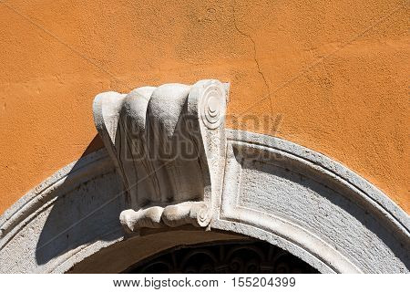 Detail of an old stone arch with ancient keystone on an orange wall. Verona Veneto Italy Europe