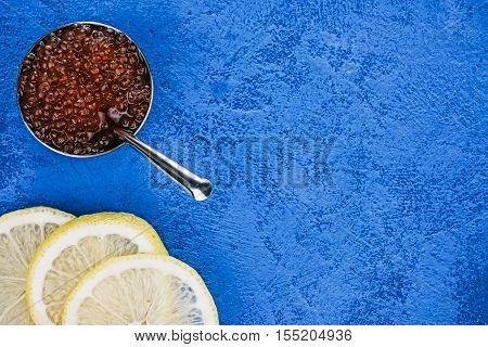 Salted salmon roe in the little steel bowl and lemon slices over spotty blue background. Closeup. Flat lay
