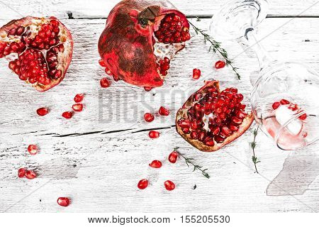 Fresh ripe pomegranate, pieces,  seeds and thrown glass over white painted old wood background