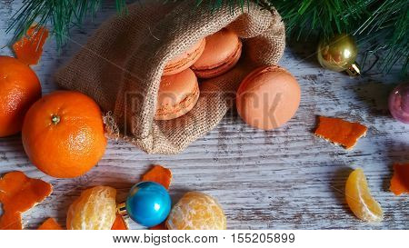 Tangerine macaroons in jute sack and Christmas tree decorations on old wooden background