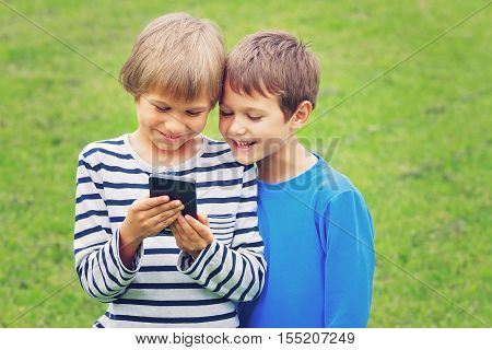 Children with mobile phone outdoor. Boys smiling looking to phone playing games or using application. Technology education leisure people concept