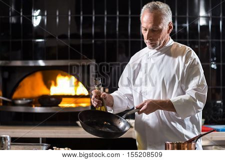 I enjoy the process of cooking. Concentrated involved aged chef holding the frying pan and the bottle of oil while standing near the table in the kitchen of a restaurant and cooking dishes