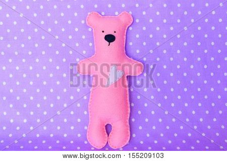 Felt bear. Pink felt bear on lavender background, hand-stitched toy
