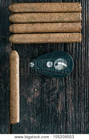 Group of cigars and cigar cutter on the dark brown wooden surface. Flat lay. Selective focus