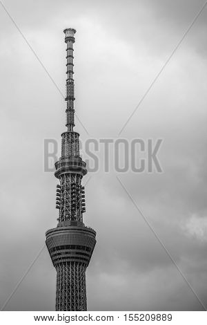 Tokyo Japan - September 28 2016: The top section of the very tall Tokyo Skytree communications tower isolated against gray rainy sky. Gray metal structure of lots of triangles.
