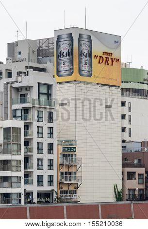 Tokyo Japan - September 28 2016: An Asahi Super Dry lager beer can billboard on top of some older apartment buildings along the Sumida River. Mostly white buildings gray sky. Beer Sign adds the color.