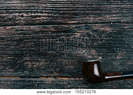 Smoking pipe in the corner on the wooden surface. Flat lay. Selective focus