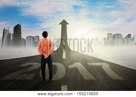 Young entrepreneur looking at upward arrow on a road while standing on the road with number 2017 symbolizing of better career in the future