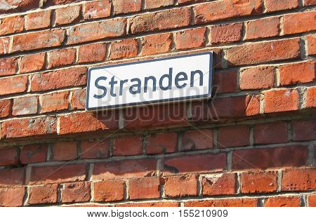 Oslo. Norway. The street name plate on the brick wall. Stranden is name of waterfront  promenade in Aker Brygge District, popular touristic place in historical part of the city.
