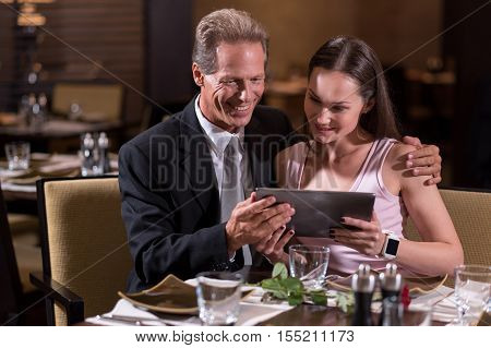 Delightful evening together. Smiling cheerful delighted couple holding the tablet and looking at it while sitting at the table in the restaurant and expressing joy