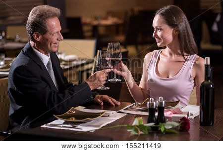 Romantic dinner. Smiling cheerful delighted couple holding wineglasses and looking at each other while sitting at the table in the restaurant and drinking wine poster