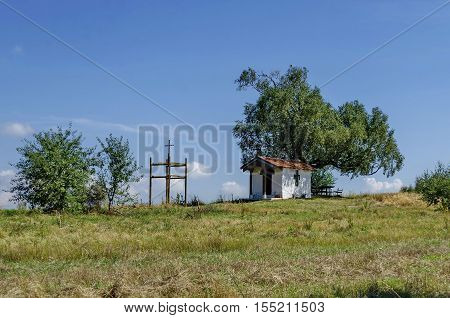 Beautiful landscape of advance summer with venerable birch tree and old chapel, located in Plana mountain, Bulgaria