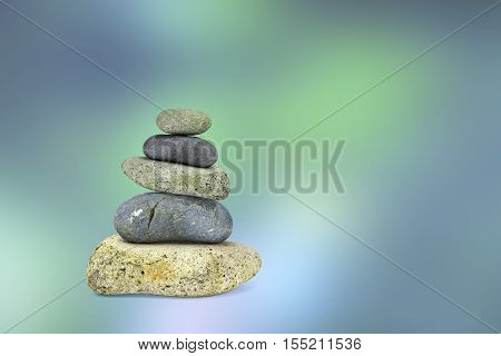 View of five balancing stones on a blue green blurred background