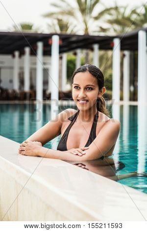 Pretty friendly Indian woman in a tropical pool standing in the cool water resting her arms on the tiles smiling happily
