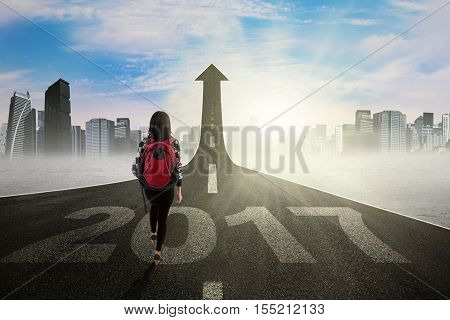 Image of student walking on the street with number 2017 toward upward arrow symbolizing of better education for the future