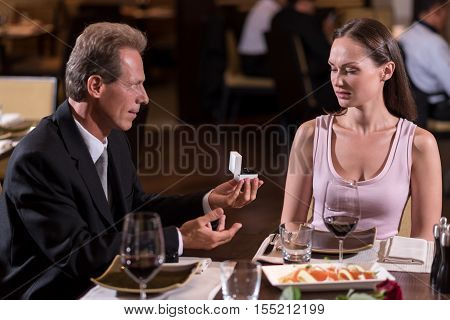 What is this. Perplexed puzzled young woman being confused from the proposal of an aged man sitting at the table in the restaurant while expressing disgust
