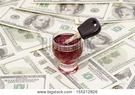 car key in a glass of wine on the background of dollars