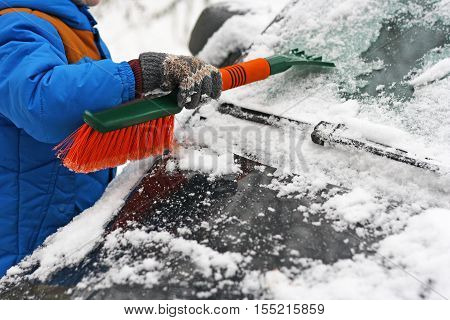 Child cleaning car from snow with an orange wool.