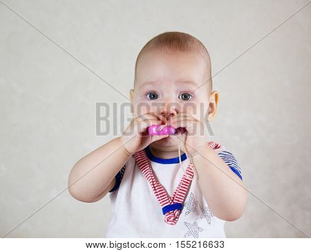 Little baby playing with toys. Small child chews on a toy