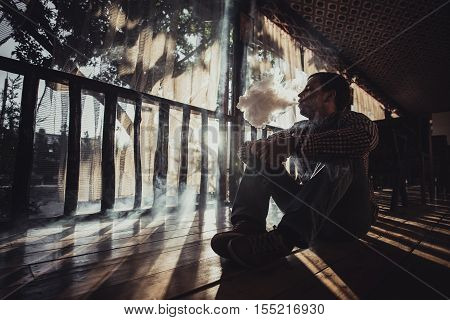 vaping young man produces vapor on sunset silhouette.