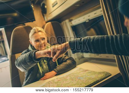 Approved RV Trip Fist Bump. Happy Couples in the Camper Motorhome Planning New Road For the Next Day Trip.