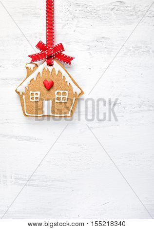 Gingerbread House Cookie with red ribbon hanging over a white painted background.