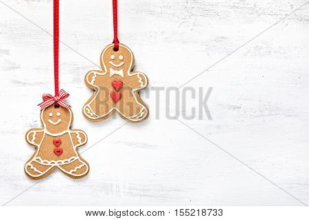 Happy Gingerbread cookie people hanging on white background.