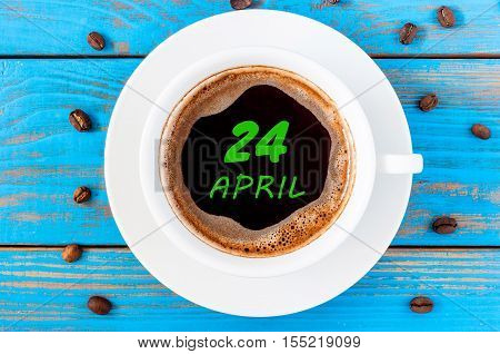April 24th. Day 24 of month, calendar written on morning coffee cup at blue wooden background. Spring time, Top view.