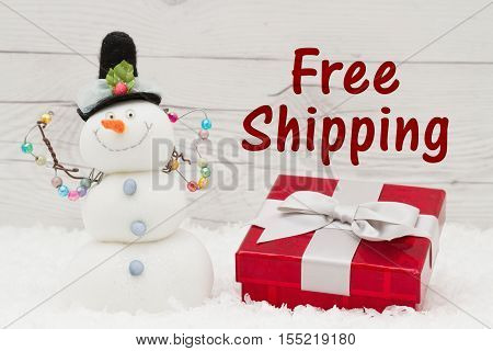 Free Shipping message Some snow Christmas present and a snowman on weathered wood with text Free Shipping