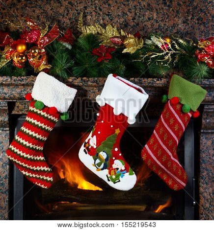 three Christmas stockings on fireplace background. Christmas time.
