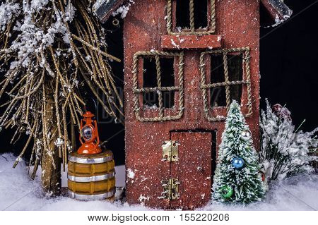 arts and crafts miniature Christmas scene of rustic house in snow with Christmas tree