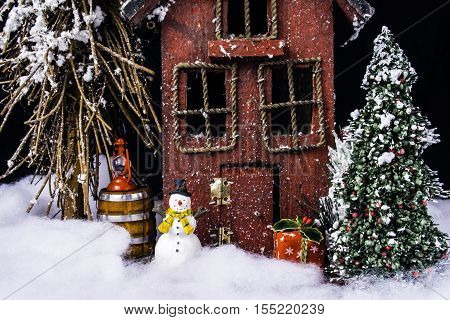 arts and crafts miniature scene of rustic house in deep snow with Christmas tree, gifts, and snowman