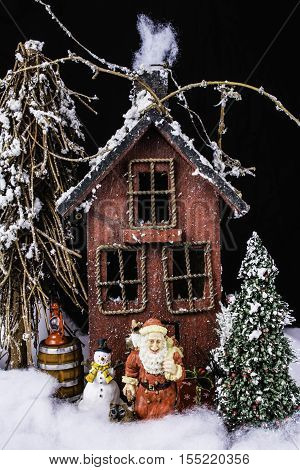 arts and crafts miniature scene of rustic house in deep snow with Santa, snowman, and Christmas tree